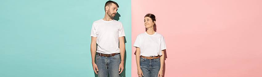 A man and a woman, both wearing white shirts, brown belts, and jeans, stand facing forward and look at each other sideways.