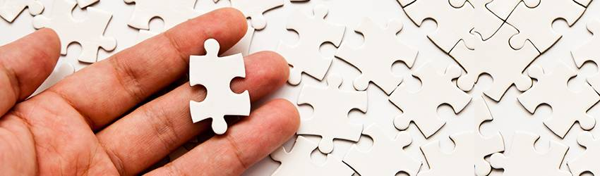 A hand holds a puzzle piece above a pile of identical puzzle pieces.