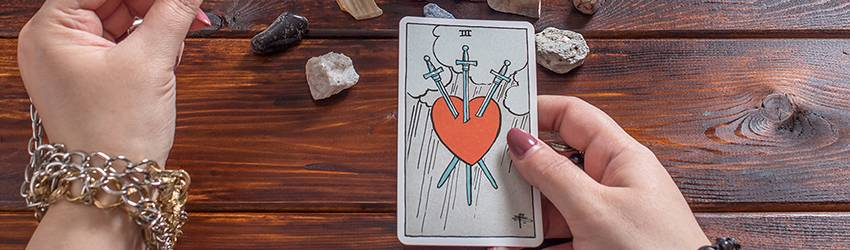 A person conducting a love reading with their Tarot cards and a red candle.