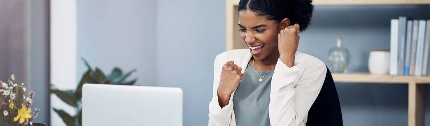 business-woman-sitting-in-her-desk-cheering