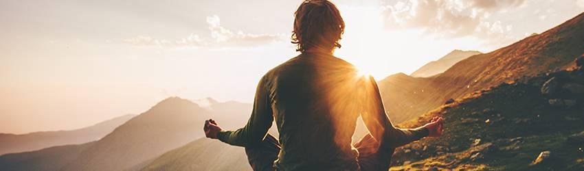 Man meditating on a mountain top.