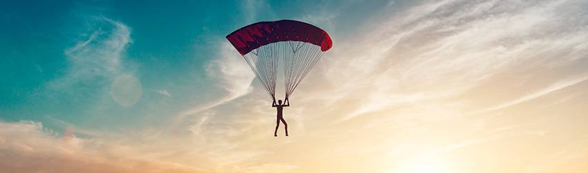 A person flying through the sky on a parachute.