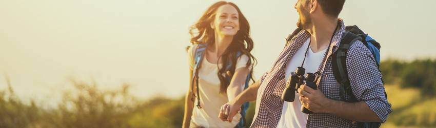 couple-smiling-holding-hands-and-hiking