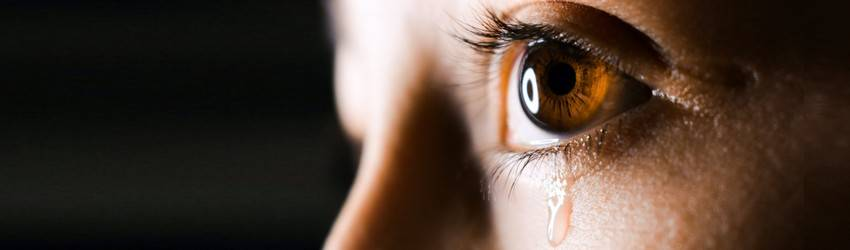 A close up of someone with hazel eyes crying on a black background.