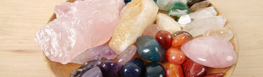 A bunch of powerful crystals in a wooden bowl.