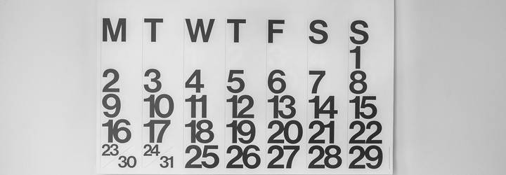 A calendar on a wall showing ever day of the week.