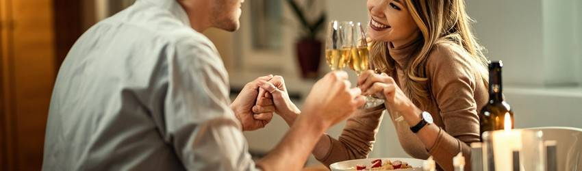 man-and-woman-on-dinner-date-holding-hands-and-drinking-wine