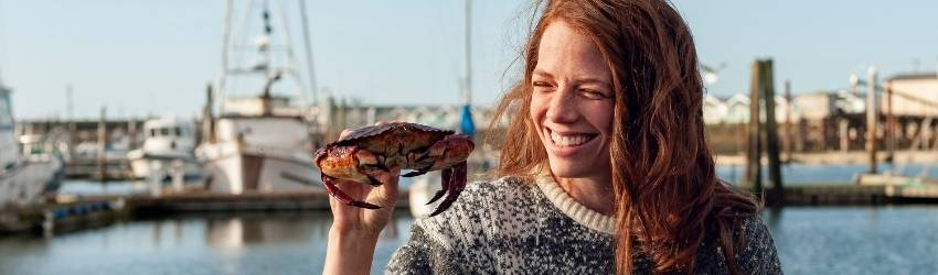 woman smiling by the water holding a crab