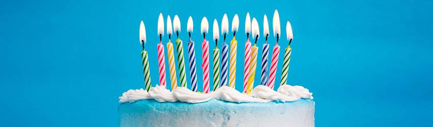 A picture of a white iced birthday cake with 12 multicolored candles, all lit. This image is on a blue background.