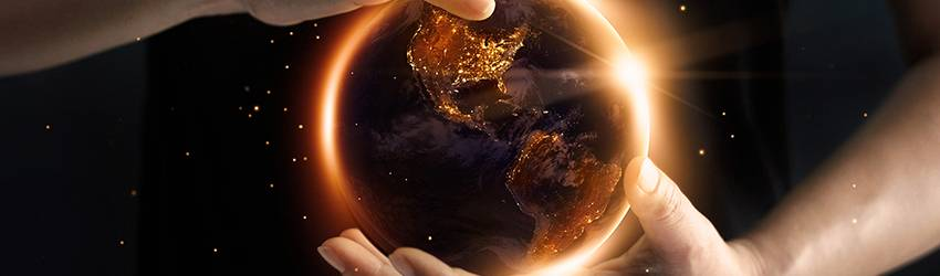 A globe rests in a persons hands. Glowing light comes from their hands.