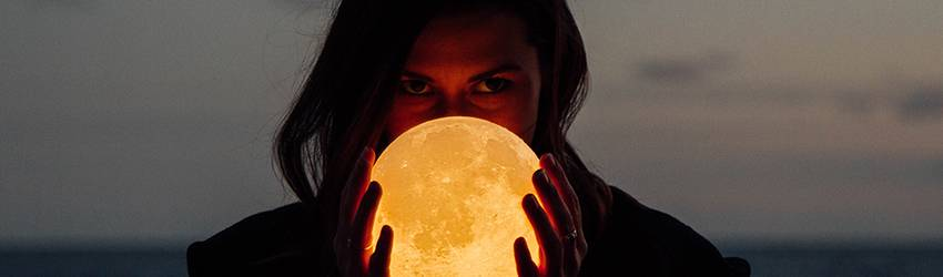 A woman holds a Full Moon lamp to obscure her face while standing in front of the ocean.