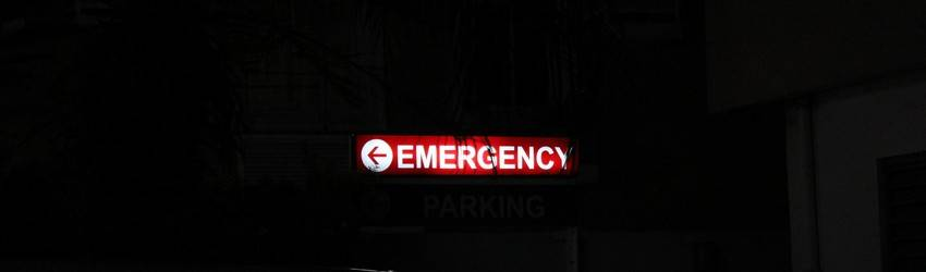 An emergency exit sign in a dark room. The sign glows red and hangs from the ceiling.