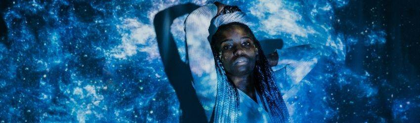 A black woman holds her hands above her head and leans against her wall. There appears to be black, white, and blue lights in a cosmic pattern in the same room.