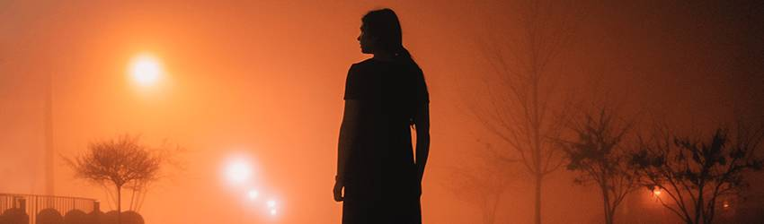 A woman is silhouetted against a smokey red sky. She looks to the left of the image and is surrounded by street lights.