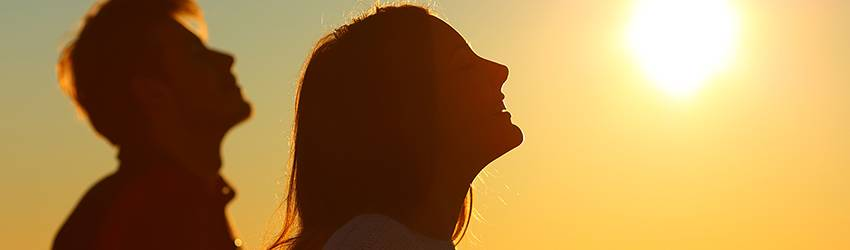 A woman stands in the energetic light of the Sun on the beach.