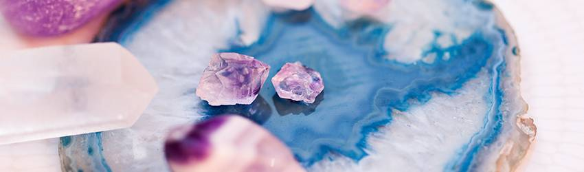 Purple quarz crystals sit on a large blue and white crystal cut.