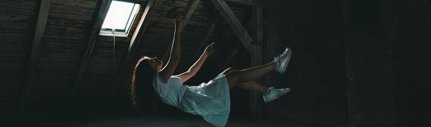 A person falling in a room. They are completely horizontal and are reaching up as if they lost their grip on something.