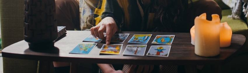 A couple sitting on the ground next to a coffee table full of tarot cards. They are close together and the woman is pointing to one tarot card in an eight card spread. It is not clear which card.