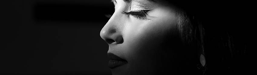 A woman sits in the shadows with only the right side of her face showing.