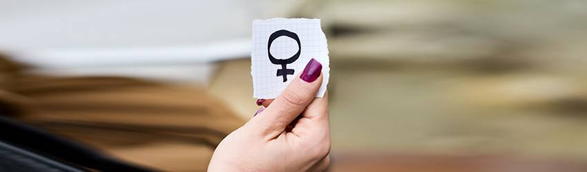 A woman holds up a piece of paper with the Venus planet symbol on it.