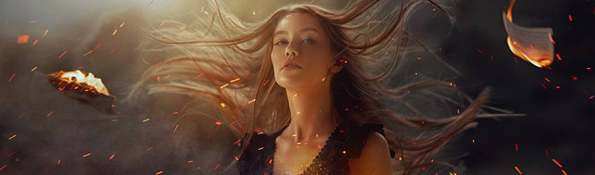 A girl with long flowing hair appears to be standing among embers, sparks, and bits of burning paper.