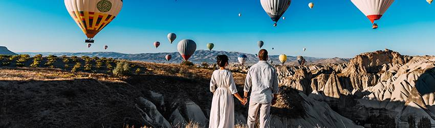 A Gemini couple stand on a cliff side watching hot air balloons float into the sky.