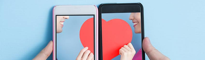 Two hands hold smart phones that are showing two people holding hearts up to each other. The heart meets and lines up at the middle of the phones.