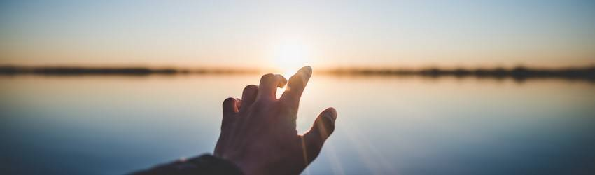 A person reaches into the horizon.