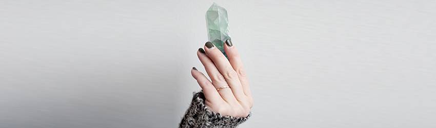 A Virgo woman holds up a green quartz crystal point in her hands.
