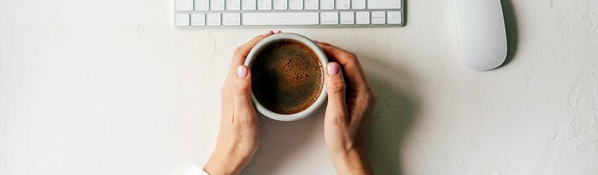 hands on desk holding a coffee cup