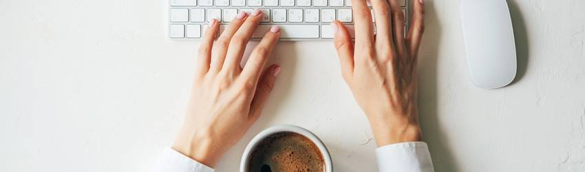 hands on keyboard with coffee cup