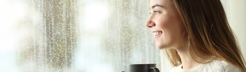 A person looks out the window with a warm cup of coffee in their hand.