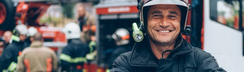 A firefighter smiles in front of his fire truck.