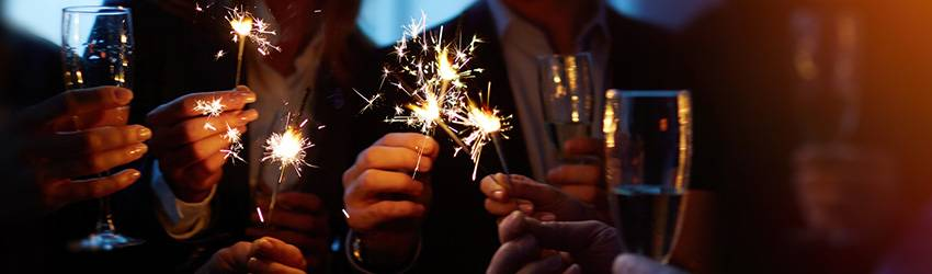 Many hands holding sparklers and champagne flutes in a toast
