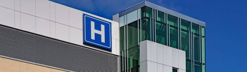 A hospital sign on the top of a building.