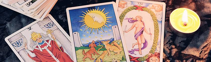 Three tarot cards sit on a table.