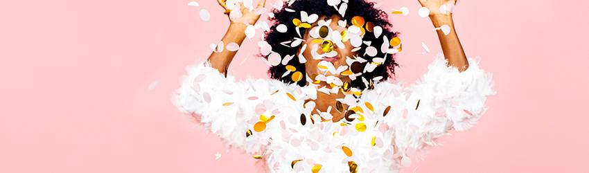 A woman is throwing colorful confetti up in front of her face on a pink background.