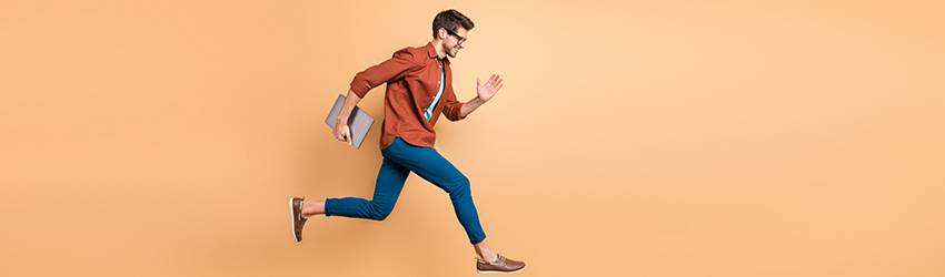 A man is jumping for joy on an orange background on his way to work because he has his crystals with him.