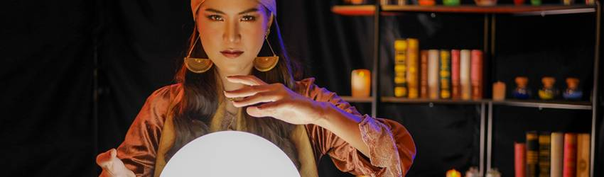 A fortune teller sits at a crystal ball - ready to give a reading.