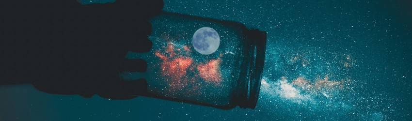 A person holds a jar up to the Moon making it seem like they have captured it.