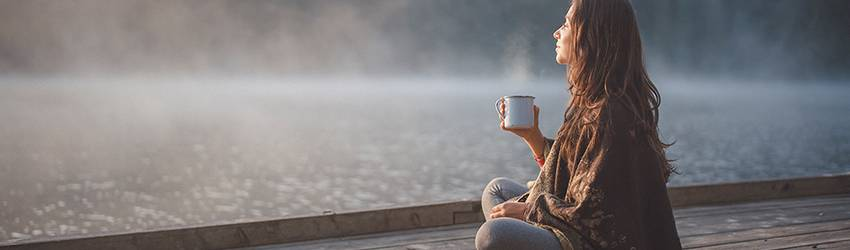 A woman sits on a dock meditating while drinking tea and looking out over the water. She is making the most of Pisces season energy.