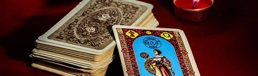 Two stacks of Tarot cards are on a red holiday table cloth.