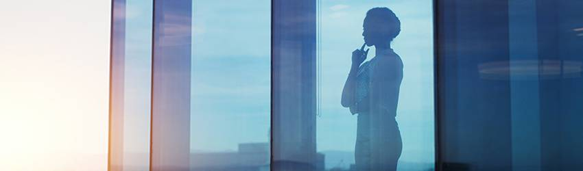 successful woman looks out skyscraper window with her finger to her chin.