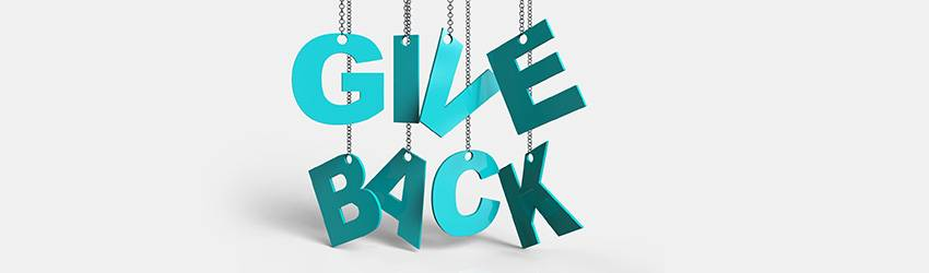 """A green sign that reads """"give back"""" hanging from silver chains. The background is a white wall."""