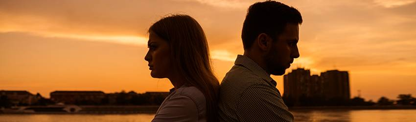 A couple sits back to back fighting as the sun sets behind them, covering the frame in a shadowy-orange hue.