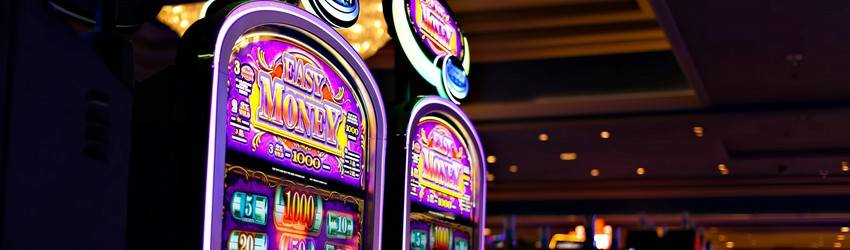 Two slot machines next to each other in a casino showing that you have won the jackpot.