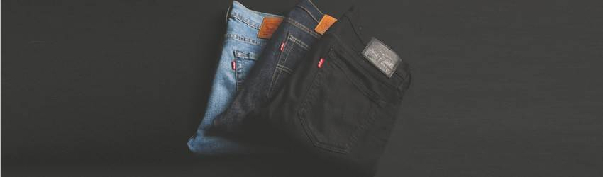 A few pairs of jeans in different washes lay square-folded on a black table.