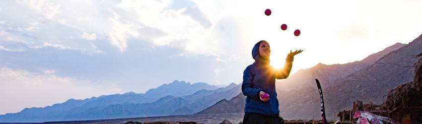 A person juggling during the sunset.