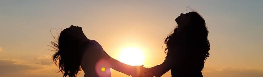 Two women dance joyously against a rising sun.
