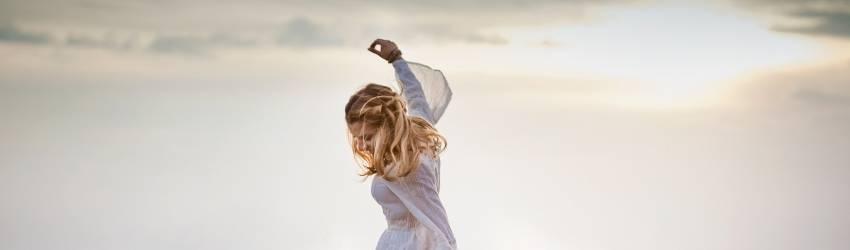 A woman dances in a field dressed in a long flowy dress.